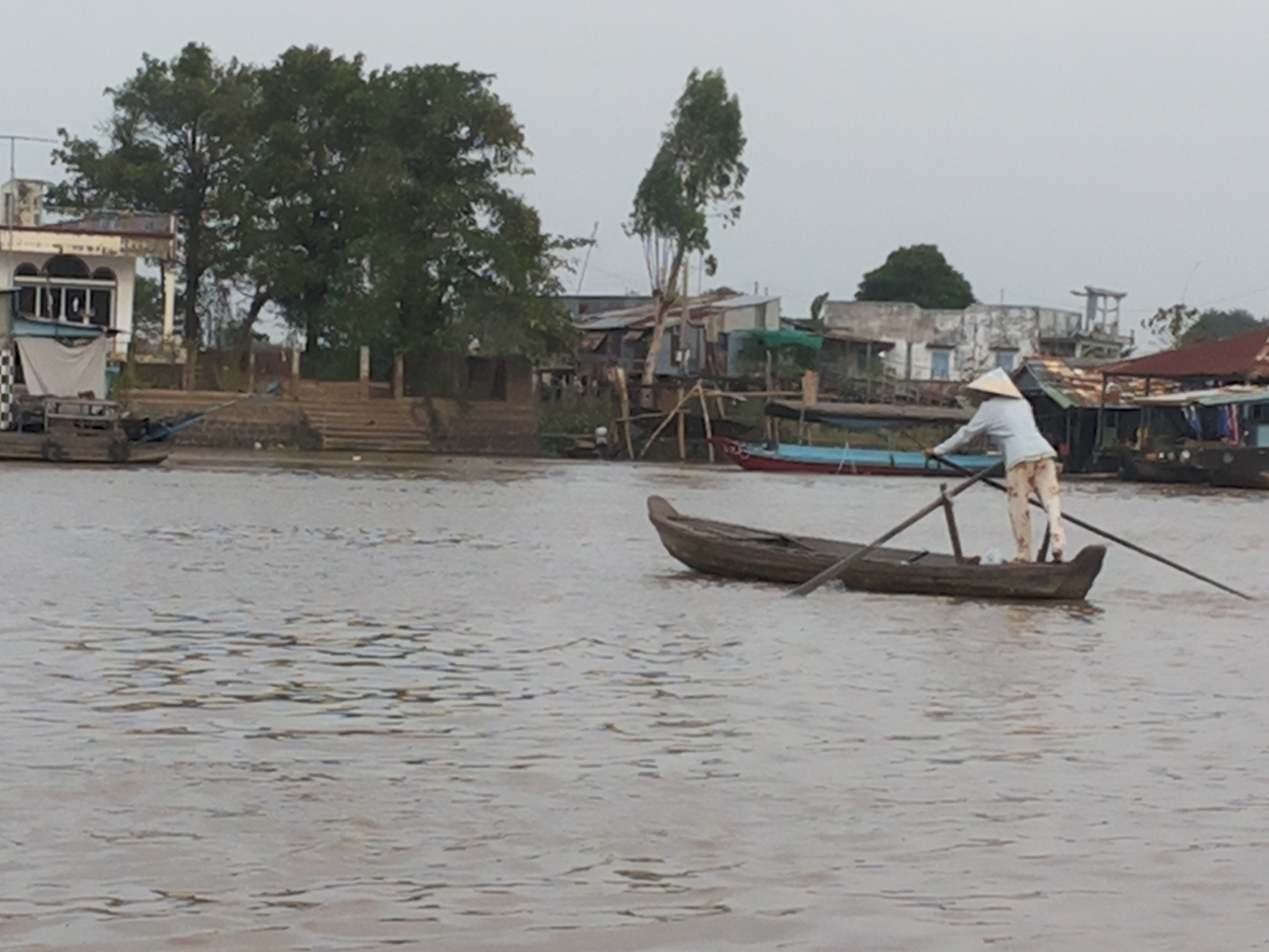 Woman rowing down the Mekong in Chau Duc